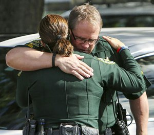 Law enforcement officers hug as other officers, not seen, escort the body of the Orange County deputy that died in the line of duty on Monday to the Orange County Medical Examiner's Office on Monday, Jan. 9, 2017, in Orlando, Fla. (Jacob Langston/Orlando Sentinel via AP)