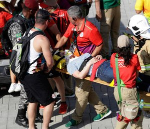An injured woman is taken away on a backboard after being struck by an overhead television camera that fell from wires suspending it over Olympic Park during the Summer Games in Rio de Janeiro, Brazil, Monday, Aug. 15, 2016.