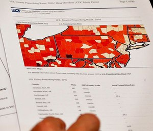 Assistant U.S. Attorney Robert Cessar shows a map illustrating the rates of opioids prescriptions by county during an interview in Pittsburgh. (AP Photo/Keith Srakocic)