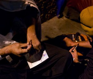 Two homeless drug addicts inject themselves with heroin in the Skid Row area of downtown Los Angeles.
