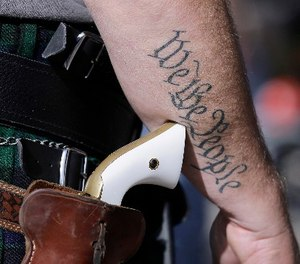 In this Jan. 26, 2015 file photo, a supporter of open carry gun laws, wears a pistol as he prepares for a rally in support of open carry gun laws at the Capitol, in Austin, Texas.