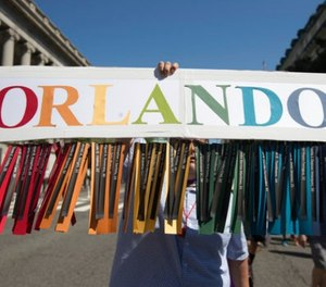 Gil Mendez, of San Francisco, holds a sign to honor the victims of the shooting at the Pulse Nightclub in Orlando, Fla., as he marches during the Equality March for Unity and Pride in Washington, Sunday, June 11, 2017. (AP Photo/Carolyn Kaster)