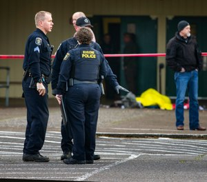 Eugene police secure the scene in front of Cascade Middle School in Eugene, Ore., Friday Jan. 11, 2019, after an officer involved shooting. (Chris Pietsch/The Register-Guard via AP)