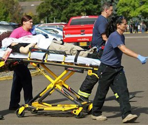 Authorities carry a shooting victim away from the scene. (Mike Sullivan/Roseburg News-Review via AP)