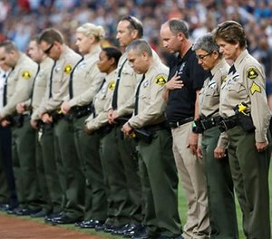 San Diego County Sheriff's Department officers stand in memory of officer Jonathan DeGuzman with a moment of silence before a baseball game between the Cincinnati Reds and the San Diego Padres on Friday, July 29, 2016, in San Diego. (Misael Virgen/San Diego Union-Tribune via AP)