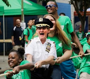 New York Police Department Deputy Chief Kathleen O'Reilly, middle, the commanding officer of Manhattan North, joins in a tug-of-war with campers from the Police Athletic League, Wednesday, July 8, 2015 in New York. The league has been serving New York City youth since 1914. (AP Photo/Mark Lennihan)