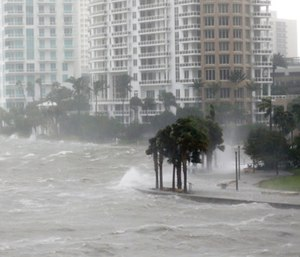 Waves crash over a seawall at the mouth of the Miami River.