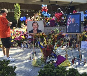 "A visitor pays his respect at a memorial for Palm Springs Police Officers Lesley Zerebny, and Jose ""Gil"" Gilbert Vega,seen in photos placed in front of the police station in Palm Springs, Calif., on Monday, Oct. 10, 2016. (AP Photo/Amy Taxin)"