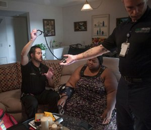 John Farris works with a patient at home.