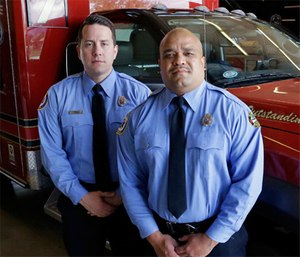 Two Orlando-based paramedics stand by their emergency vehicle.