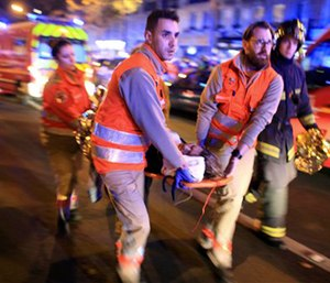 A woman is evacuated from the Bataclan concert hall after a shooting in Paris on Nov. 13.