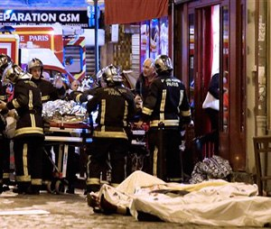 Rescue workers gather at victims in the 10th district of Paris, Friday, Nov. 13, 2015. (AP Photo/Jacques Brinon)