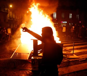 Demonstrators gather around a burning barricade during clashes with riots police, in Paris, France, Saturday, Dec. 8, 2018. (AP Photo/Thibault Camus)
