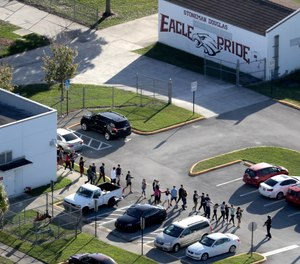 In this Wednesday, Feb. 14, 2018 file photo, students are evacuated by police from Marjory Stoneman Douglas High School in Parkland, Fla., after a shooter opened fire on the campus.