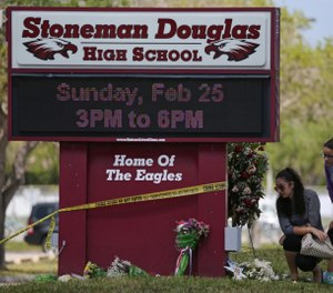 Mourners bring flowers as they pay tribute at a memorial for the victims of the shooting at Marjory Stoneman Douglas High School on Sunday, Feb. 25, 2018 during an open house as parents and students returned to the school for the first time since 17 people were killed in a mass shooting at the school in Parkland on Feb. 14, 2018. (David Santiago/Miami Herald/TNS)
