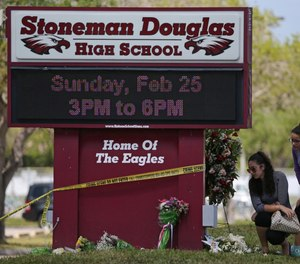 Mourners bring flowers as they pay tribute at a memorial for the victims of the shooting at Marjory Stoneman Douglas High School on Sunday, Feb. 25, 2018 during an open house as parents and students returned to the school for the first time since 17 people were killed in a mass shooting at the school in Parkland on Feb. 14, 2018.