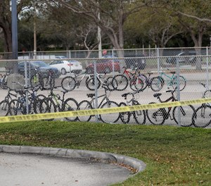 Un-retrieved bicycles appear inside the fence of Marjory Stoneman Douglas High School, Sunday, Feb. 18, 2018. (AP Photo/Gerald Herbert)
