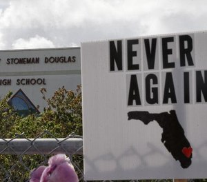 Memorial signs rest on a fence surrounding Marjory Stoneman Douglas High School in Parkland, Florida on February 21, 2018.