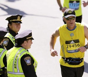 """In this April 18, 2016 file photo, actor Mark Wahlberg, center left, dressed as a Boston Police officer, watches runners cross the finish line as he films a scene for the """"Patriot's Day"""" movie at the 120th Boston Marathon in Boston. (AP Photo/Charles Krupa, File)"""
