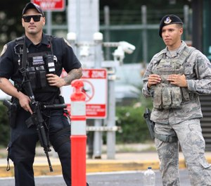 Security stands guard outside the main gate at Joint Base Pearl Harbor-Hickam in Hawaii. A shooting at the base Wednesday left 3 dead. (Photo/AP/Caleb Jones)