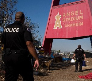 Two police officers, Eric Meier, right, and Curtis Bynum from the Anaheim Police Department's homeless outreach team walk through a homeless encampment set up outside Angel Stadium to hand out flyers about the community outreach day Tuesday, Dec. 19, 2017, in Anaheim, Calif.