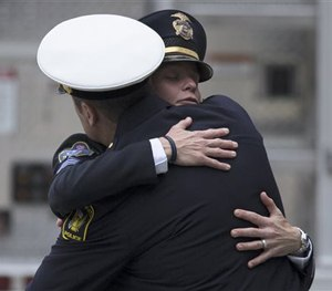 Mourners hug as they arrive at the Cintas Center at Xavier University for the memorial of slain Cincinnati Police Officer Sonny Kim, Thursday, June 25, 2015, in Cincinnati.
