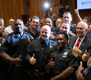 Vice President Mike Pence, right, meets with members of the New York Police Department's football team. (AP Photo/Mark Lennihan)