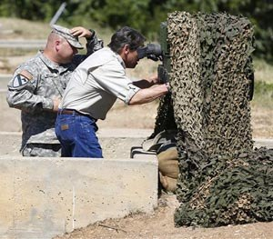 Gov. Rick Perry examines an advanced optics system at Camp Swift in Bastrop, Texas on Wednesday, Aug. 13, 2014. (AP Image)