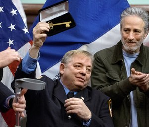 In this Jan. 9, 2016, file photo, retired Fire Department of New York firefighter and Sept. 11 first responder Ray Pfeifer, left, holds the key to the city he was given at New York's City Hall, and is applauded by Jon Stewart. (AP Photo/Craig Ruttle, File)