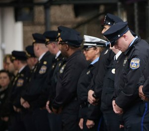 Philadelphia police officers line up after the body of SWAT Cpl. James O'Connor was brought to a hearse at the emergency room entrance at Temple University Hospital in Philadelphia on Friday, March 13, 2020. O'Çonnor was shot and killed early Friday as he served a homicide warrant at a home in the city's Frankford section. (Tim Tai/The Philadelphia Inquirer via AP)