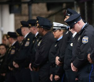 Philadelphia police officers line up after the body of SWAT Cpl. James O'Connor was brought to a hearse at the emergency room entrance at Temple University Hospital in Philadelphia on Friday, March 13, 2020.
