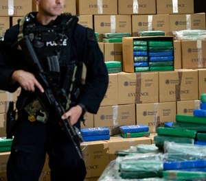 An officer stand guard over a fraction of the cocaine seized from a ship at a Philadelphia port that was displayed at a news conference at the U.S. Custom House in Philadelphia, Friday, June 21, 2019.  (AP Photo/Matt Rourke)