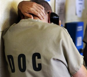 In this June 26, 2014, file photo, an inmate uses a phone at the Cook County Jail in Chicago.