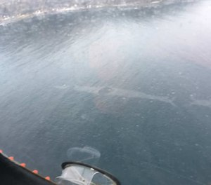 This aerial photo shows a 1,500-foot-long sheen left on the surface of the Unalaska Bay following the crash of a medevac plane into the waters. All three crewmembers on board the flight survived and were rescued. (Photo/U.S. Coast Guard)