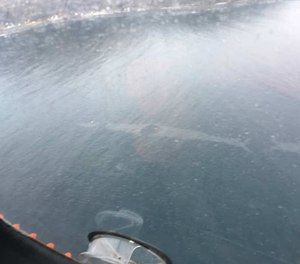 This aerial photo shows a 1,500-foot-long sheen left on the surface of the Unalaska Bay following the crash of a medevac plane into the waters. All three crewmembers on board the flight survived and were rescued.