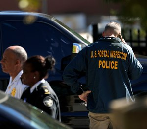 Law enforcement officials gather outside a U.S. post office facility after reports that a suspicious package was found in Atlanta, Monday, Oct. 29, 2018.