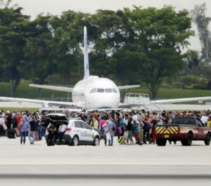 People stand on the tarmac at the Fort Lauderdale-Hollywood International Airport after a shooter opened fire inside a terminal of the airport, killing several people and wounding others before being taken into custody, Friday, Jan. 6, 2017, in Fort Lauderdale, Fla. (AP Photo/Lynne Sladky)
