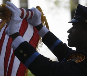An officer rolls up a flag during a ceremony at the New York State Police Officers' Memorial on Tuesday, May 10, 2016, in Albany, N.Y.