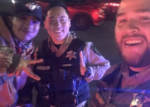 Marvin, a hitchhiker who was trying to make it to court, poses with deputies Redden and Yoon.