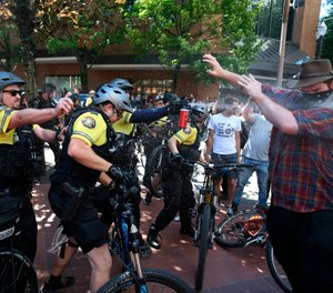After a confrontation between authorities and protestors, police use pepper spray as multiple groups, including Rose City Antifa, the Proud Boys and others protest in downtown Portland, Ore., on Saturday, June 29, 2019. (Dave Killen/The Oregonian via AP)