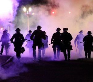 In this March 29, 2020, file photo, police officers walk enveloped by teargas in Portland, Ore., a liberal city with a reputation for full-throated and frequent protests.
