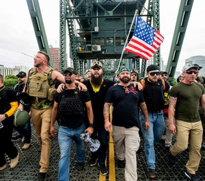 "Members of the Proud Boys and other right-wing demonstrators march across the Hawthorne Bridge during an ""End Domestic Terrorism"" rally in Portland, Ore., on Saturday, Aug. 17, 2019. (AP Photo/Noah Berger)"