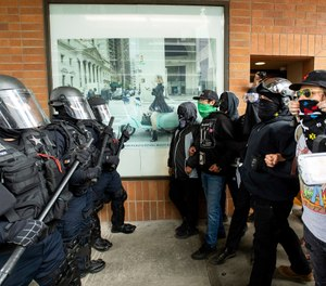 "Police officers face off against protesters opposed to right-wing demonstrators following an ""End Domestic Terrorism"" rally in Portland, Ore., on Saturday, Aug. 17, 2019. (AP Photo/Noah Berger)"