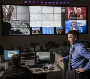 "Jeff Brantingham, anthropology professor at UCLA, displays computer generated ""predictive policing"" zones at the LAPD Unified Command Post in Los Angeles. (AP Image)"