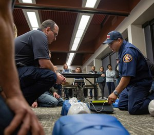 Luis Gonzalez, a Community Emergency Response Team instructor from the Los Angeles County Fire Department, shows trainees how to attach an automated external defibrillator during a CPR demonstration.
