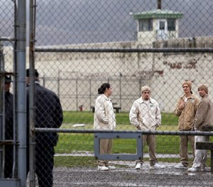 In this file photo, inmates mingle in a recreation yard in view of guards, left, at the Monroe Correctional Complex in Monroe, Wash.