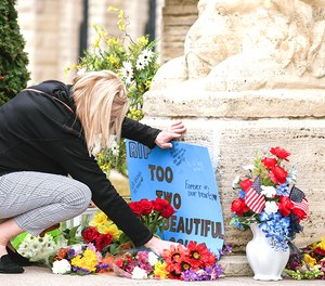 A woman adjusts a sign next to memorials to the two Anamosa State Penitentiary staff who were killed in an escape attempt. The aftermath of the attack has been felt by offenders at all state prisons.