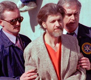 In this April 4, 1996 file photo Theodore John Kaczynski is flanked by federal agents as he is led to a car from the federal courthouse in Helena, Mont.