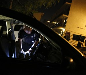 An officer searches a car after a shooting was reported outside an apartment building on Feb. 17, 2015 in Los Angeles. (Michael Robinson Chavez/Los Angeles Times/TNS Image)