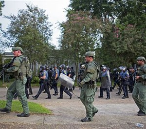Police retreat through a residential neighborhood after dispersing protesters in Baton Rouge, La. on Sunday, July 10, 2016. After an organized protest in downtown Baton Rouge protesters wondered into residential neighborhoods and toward a major highway that caused the police to respond by arresting protesters that refused to disperse. (AP Photo/Max Becherer)